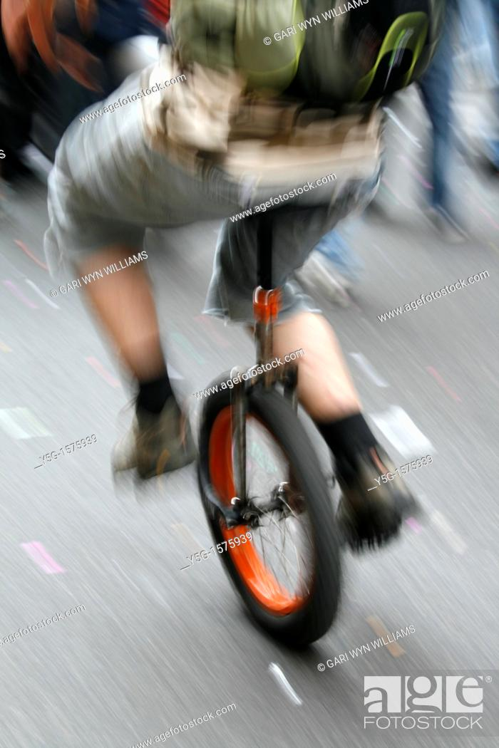 Stock Photo: fast unicycle rider in town.