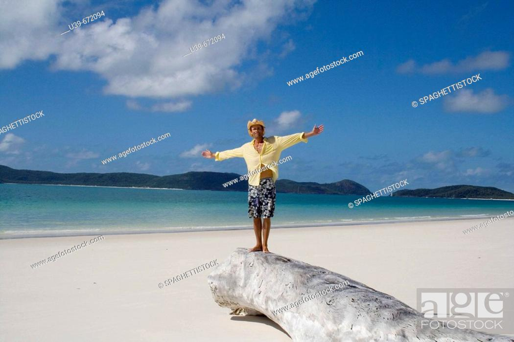 Stock Photo: Man with arms outstretched.  Whitehaven Beach, Australia.