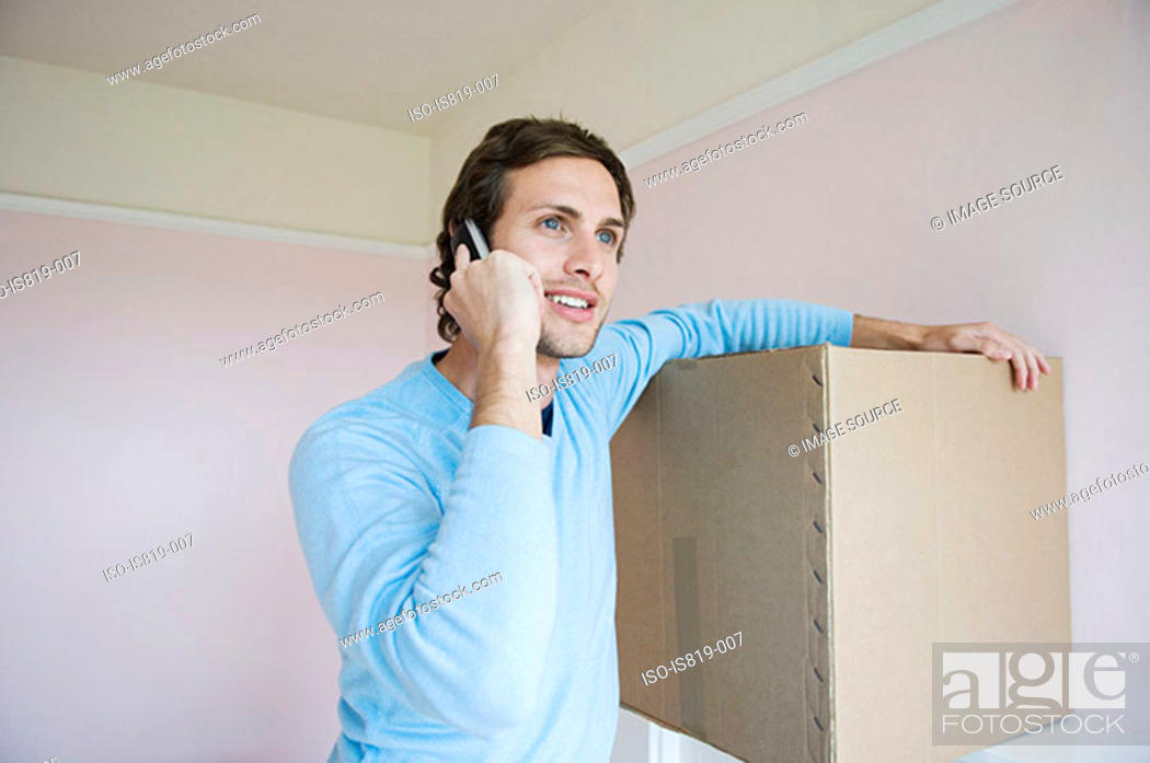 Stock Photo: Man on mobile phone with cardboard box.