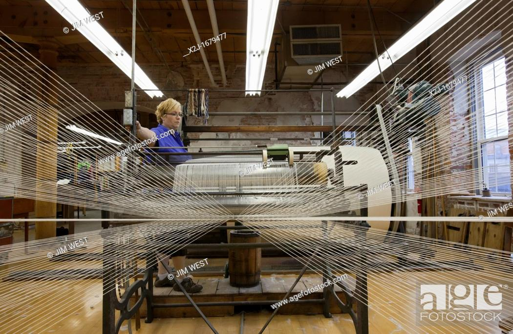 Stock Photo: Amana, Iowa - A worker runs a warping creel at the Amana Woolen Mill  The machine gathers up to 240 strands of yarn that will later be woven into cloth on a.