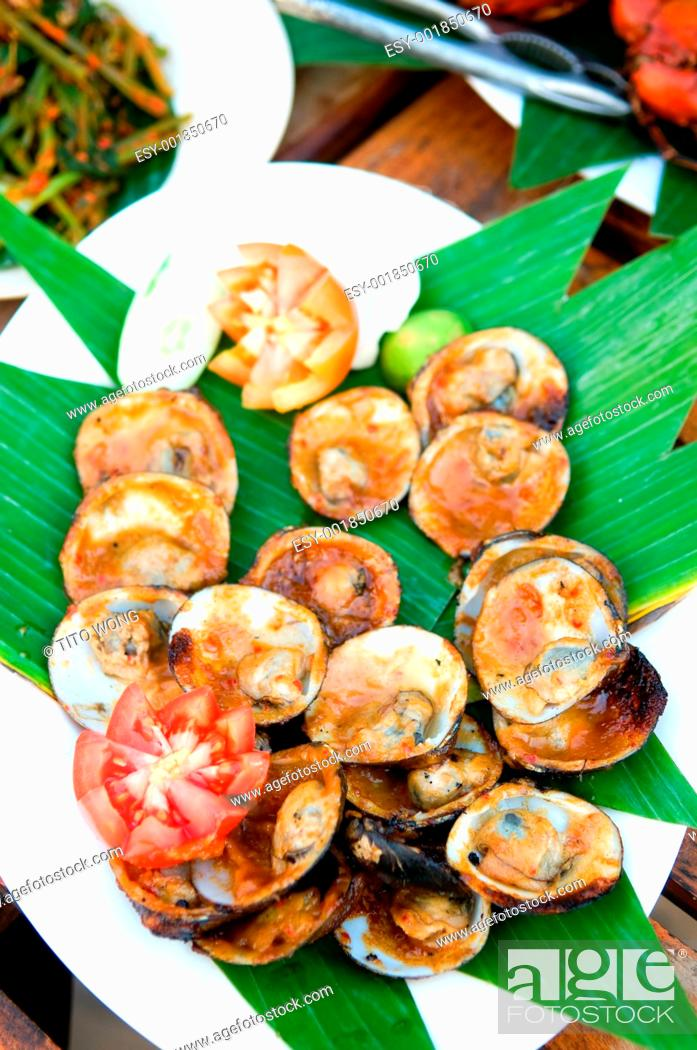 Stock Photo: Grilled shell fish split in shell with garnish.