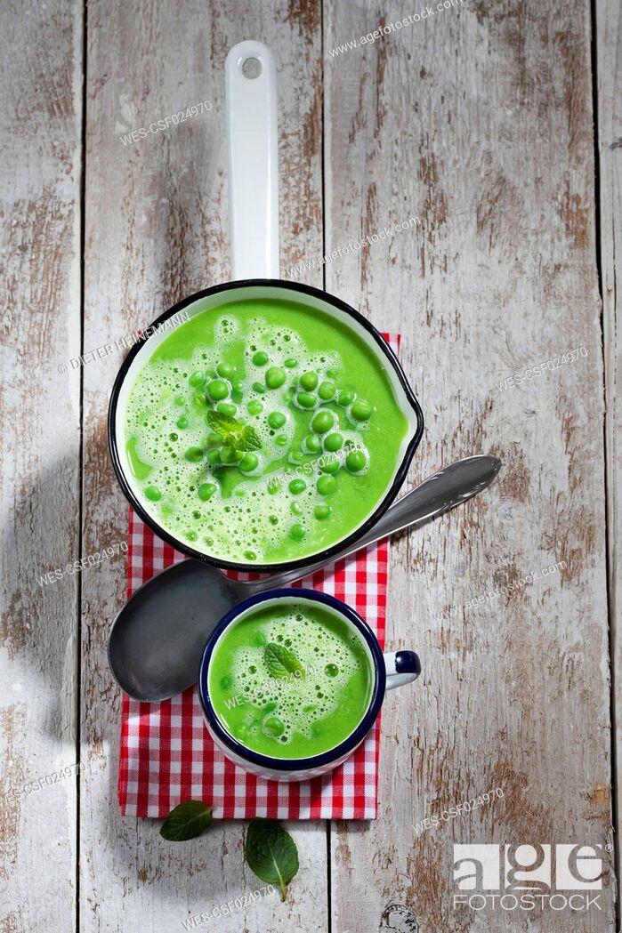Stock Photo: Saucepan and mug of pea soup, spoon and cloth on wood.