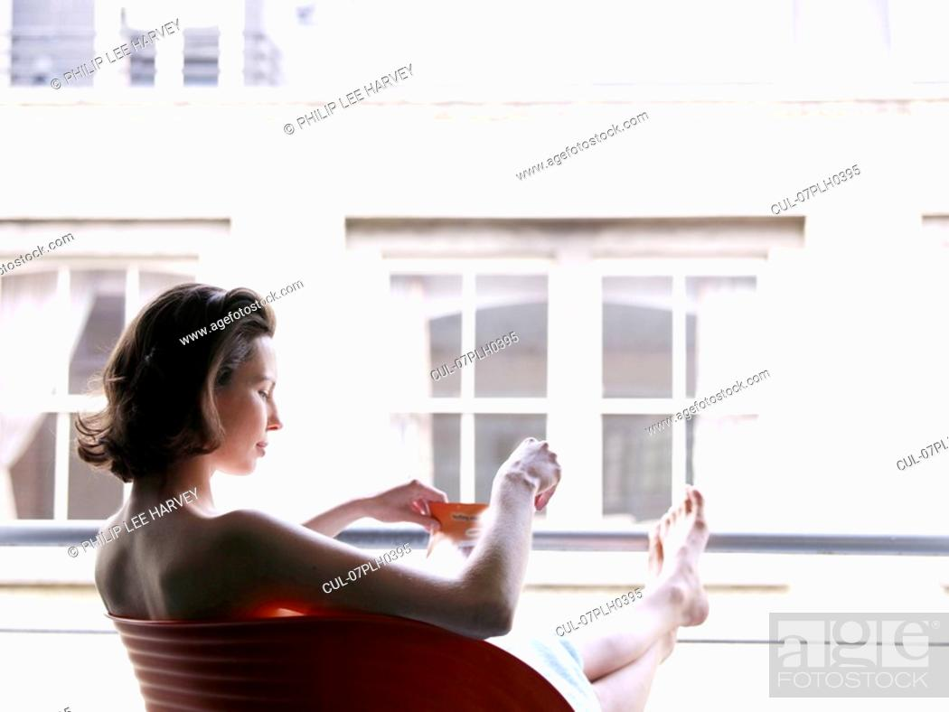 Stock Photo: Woman sitting at window with a drink.