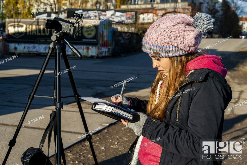 Stock Photo: Berlin, Germany. Young, Brazilian girl filming RAW-Gelande, a creative and urban hotspot onside former Eastern Berlin for her Youtube Chanel.