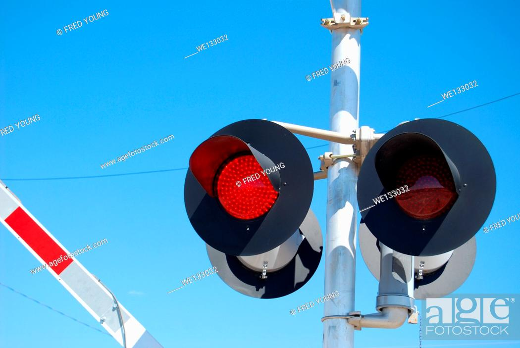Stock Photo: Flashing warning lights at a railroad crossing while the gate is being lowered.