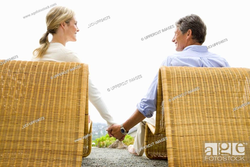 Stock Photo: Couple sitting on patio chairs and holding hands.
