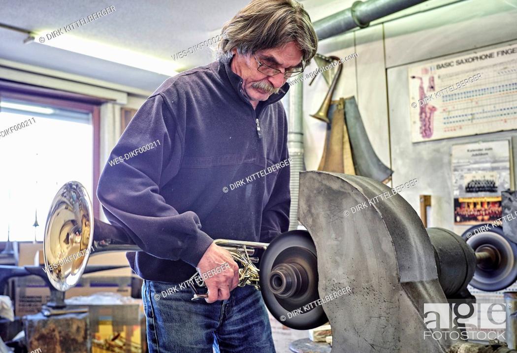 Imagen: Instrument maker polishing trumpet in workshop.
