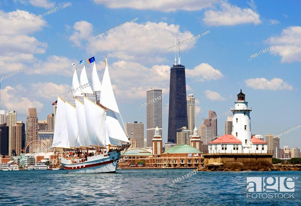 Stock Photo: Chicago tour boat 'Windy' leaving Navy Pier and heading out onto Lake Michigan past the historic Chicago Lighthouse  Tall dark building is the John Hancock.
