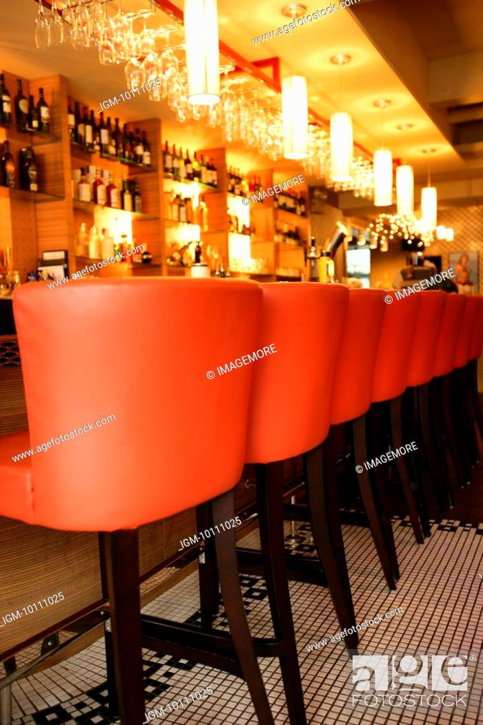 Stock Photo: Bar stools in a row in front of bar counter with modern style.