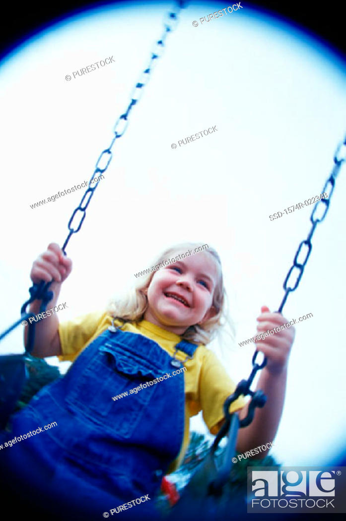 Stock Photo: Low angle view of a girl sitting on a swing.