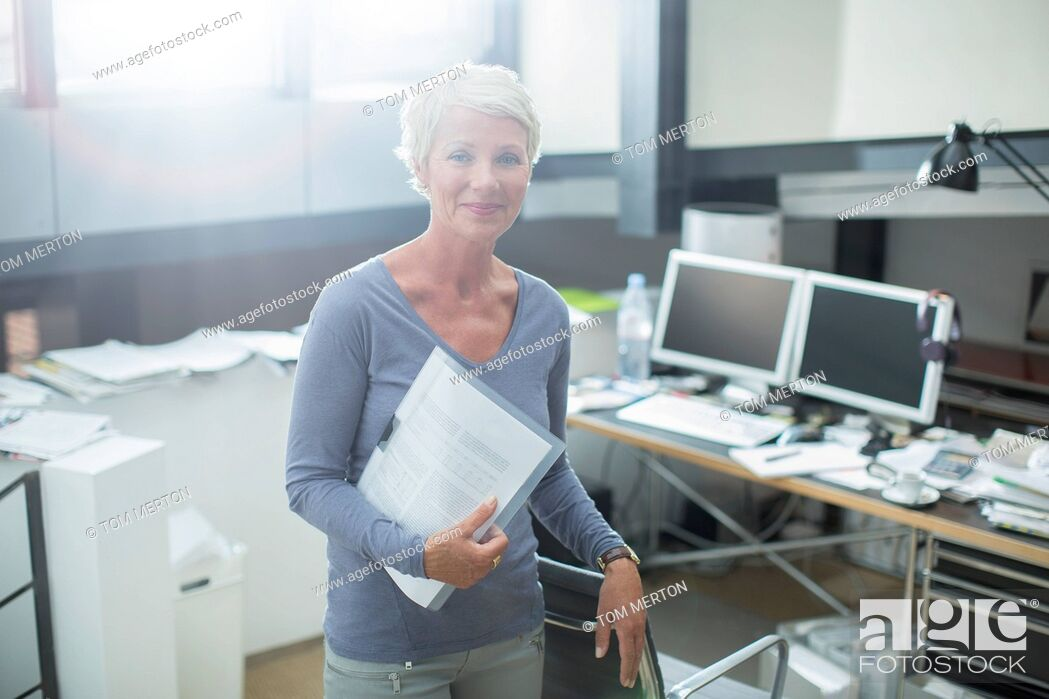 Stock Photo: Businesswoman carrying paperwork in office.