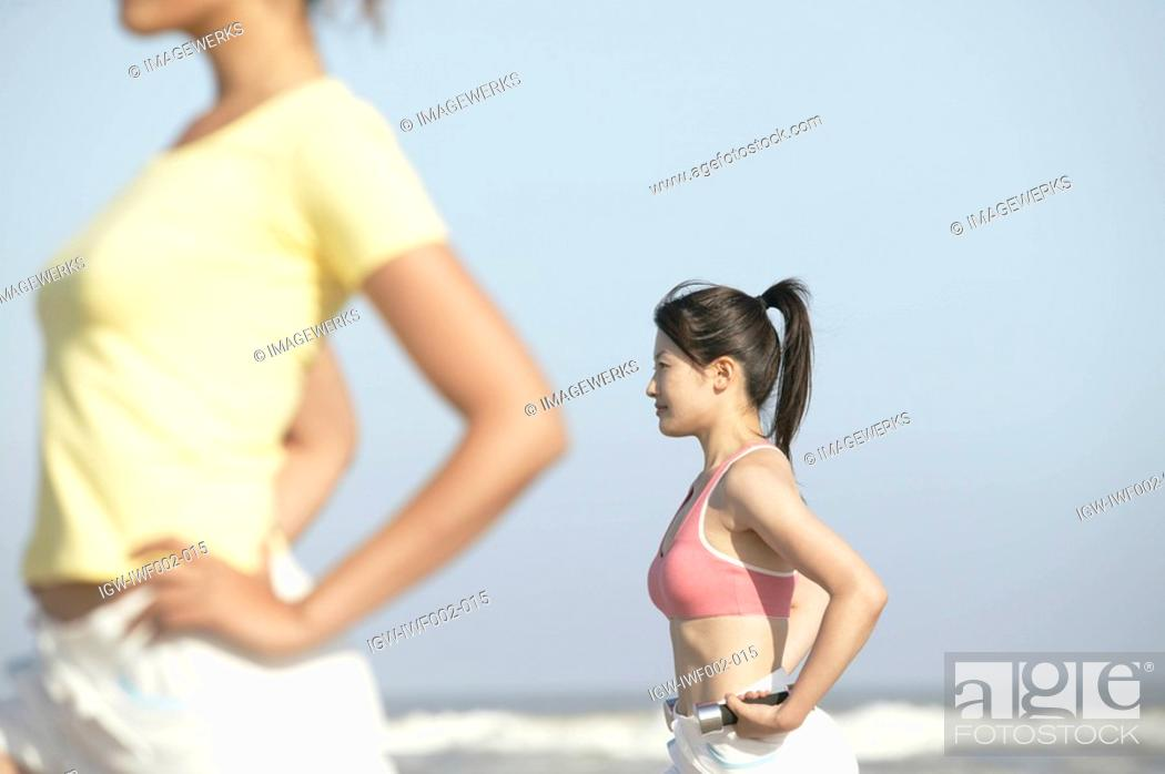 Stock Photo: Two young women stand at the seashore with dumbbell in on of the womans hand.