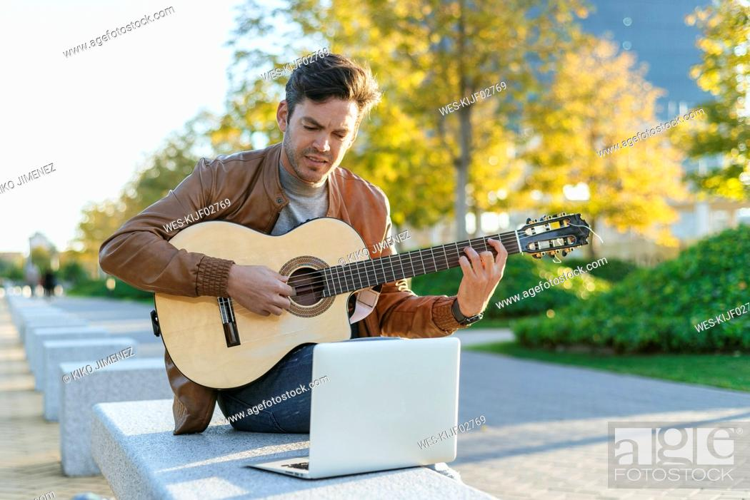 Stock Photo: Man with laptop playing guitar in the city, Madrid, Spain.
