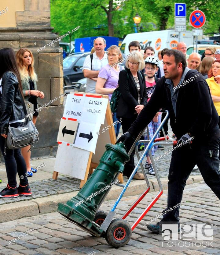 Stock Photo: A person transports a fire hydrant to a film set in Halberstadt, Germany, 17 May 2013. US film star George Clooney was at set to shoot the film 'The Monuments.