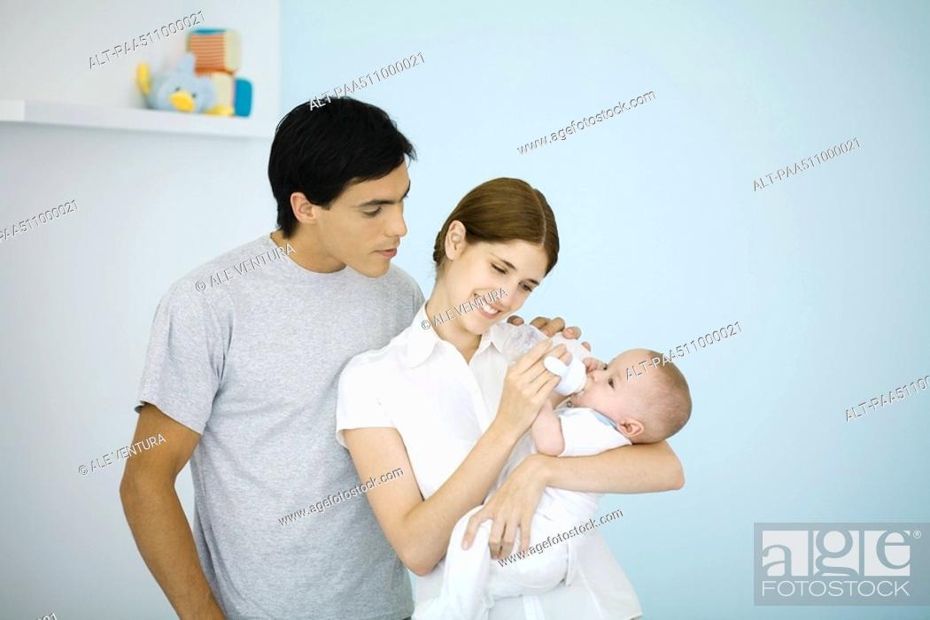 Stock Photo: Mother feeding baby with a bottle, husband watching over her shoulder.