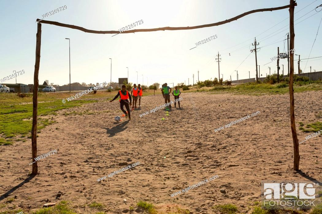 Stock Photo: Kids playing football in the ground.