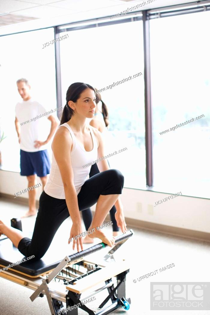Stock Photo: Woman working out on pilates equipment.