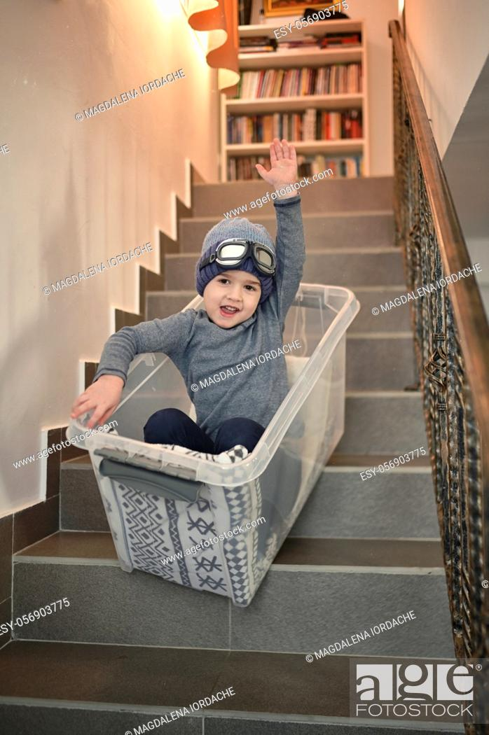 Stock Photo: Little Boy having fun sledding down stairs in a storage box.