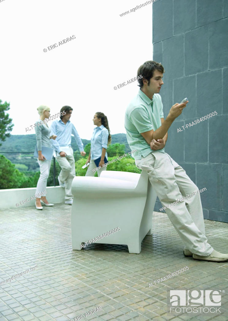 Stock Photo: Casually dressed young executives standing on terrace, man in foreground using cell phone.