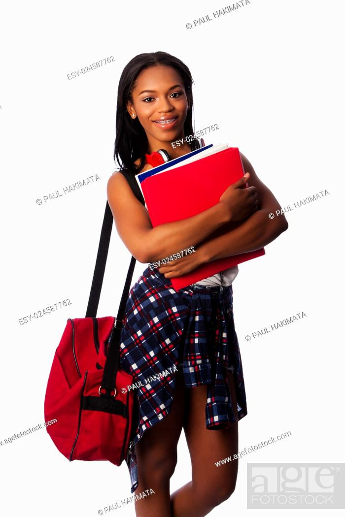 Stock Photo: Beautiful happy student standing with binders, books, notepads and bag, on white.