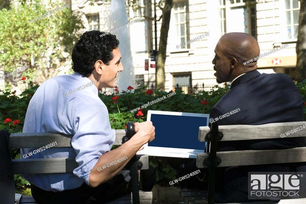 Stock Photo: Rear view of two businessmen sitting in a park.