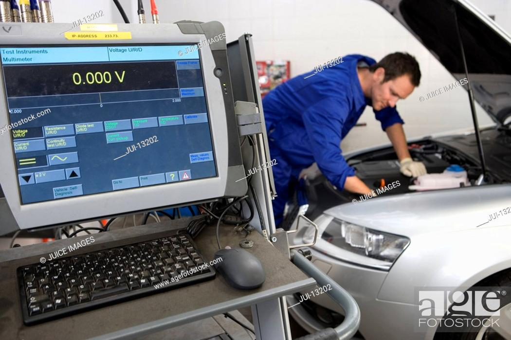 Stock Photo: Mechanic working on car by computer.