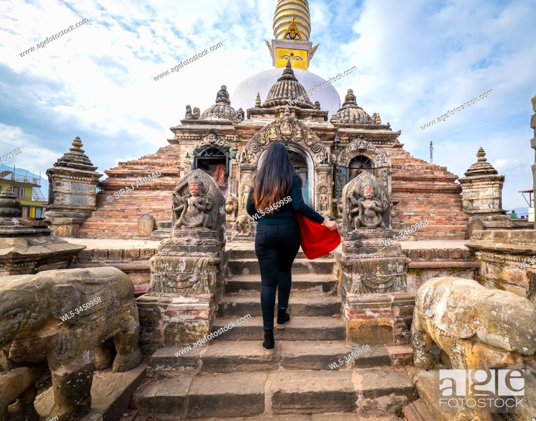 Stock Photo: Young girl walks towards a Sacred Buddhist Monastery. Sculptures of Gods and Goddesses carved on the stone of Ancient Buddhist Temple and ancient ruins.