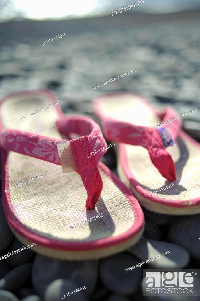 Stock Photo: A pair of pink flip flops shoes on a pebble beach, summer UK.