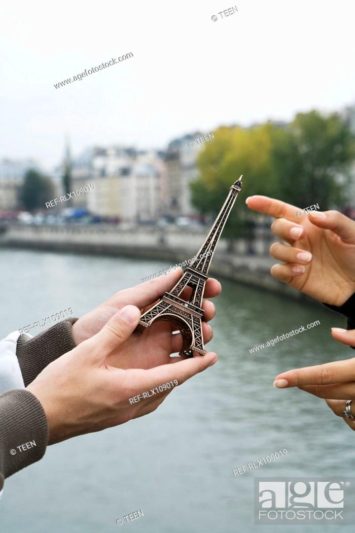 Stock Photo: Close up of young man giving present of miniature Eiffel Tower to woman.