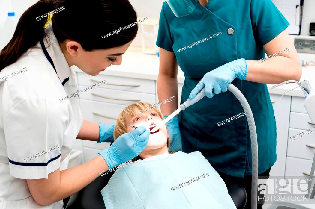 Stock Photo: Dentist and assistant curing little girl.