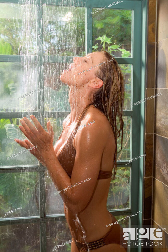 Stock Photo: Young woman in brown bathing suit rinses off in shower.