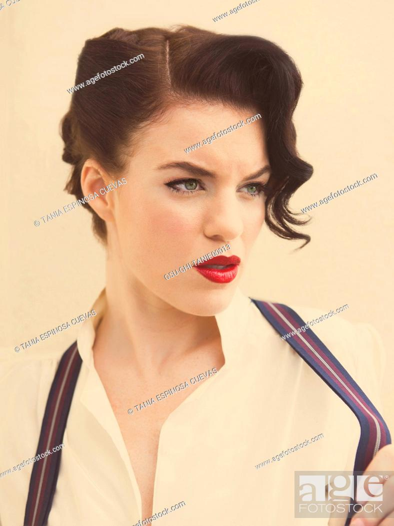 Stock Photo: Portrait of Intense Young Adult Woman Tugging on Suspenders.