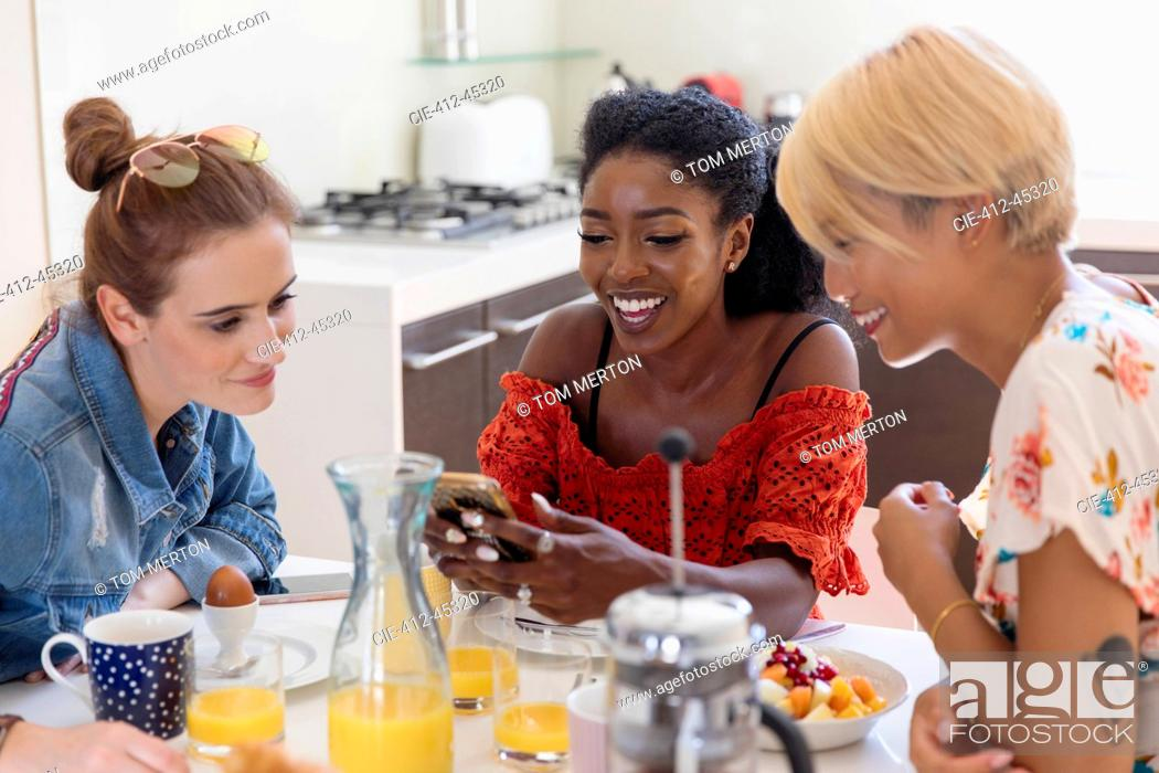 Stock Photo: Young women friends enjoying breakfast, using smart phone in kitchen.