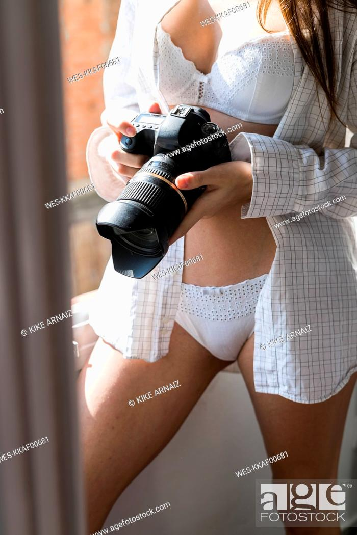 Stock Photo: Young woman with camera wearing lingerie, partial view.