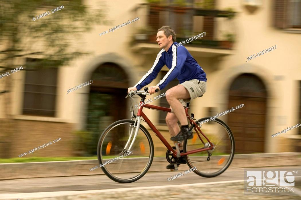 Stock Photo: Italy, Lombardy, Campione, Man mountain biking through village.