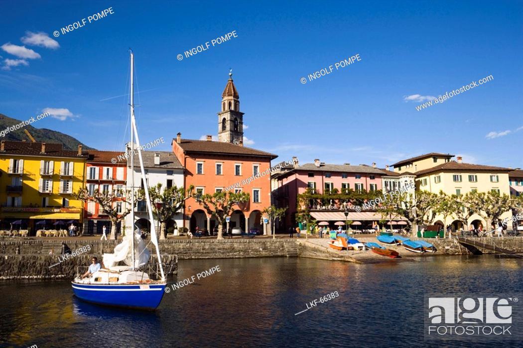 Imagen: Sailling boat on Lake Maggiore, harbour promenade with spire of church Santi Pietro Paolo in background, Ascona, Ticino, Switzerland.