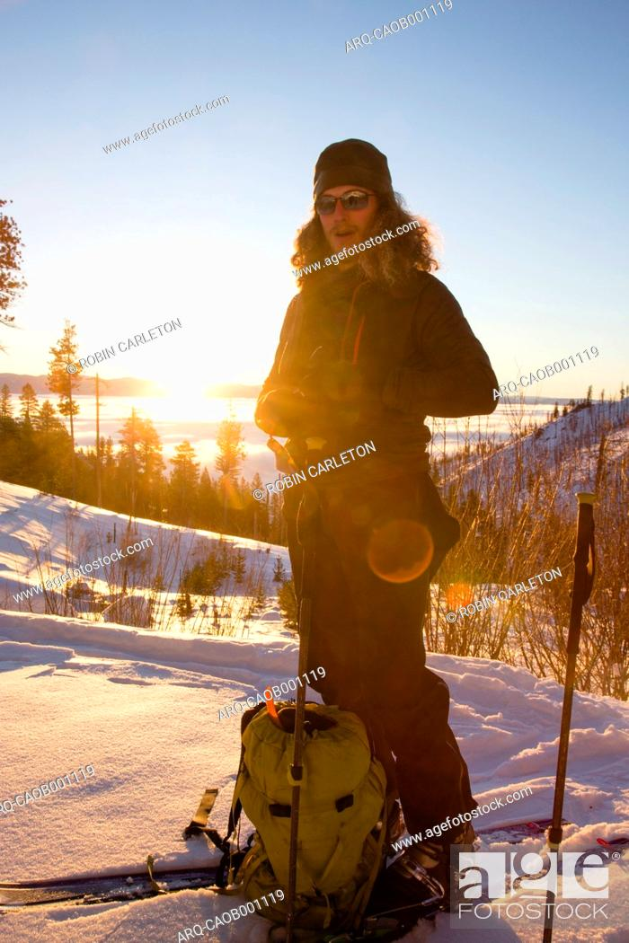 Stock Photo: Portrait of backcountry skier with backpack taking break at sunrise.