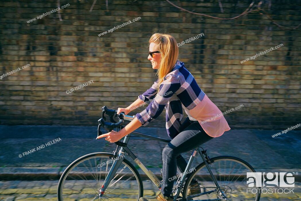 Imagen: Side view of mid adult woman cycling on bicycle.