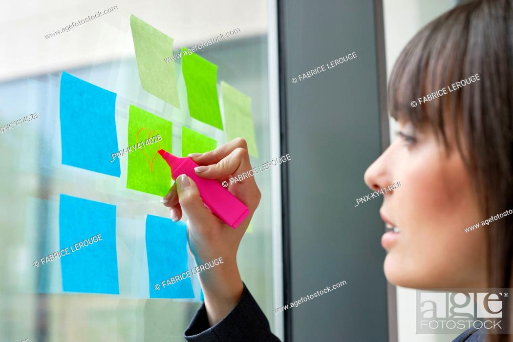 Stock Photo: Businesswoman drawing heart shape on an adhesive note in an office.