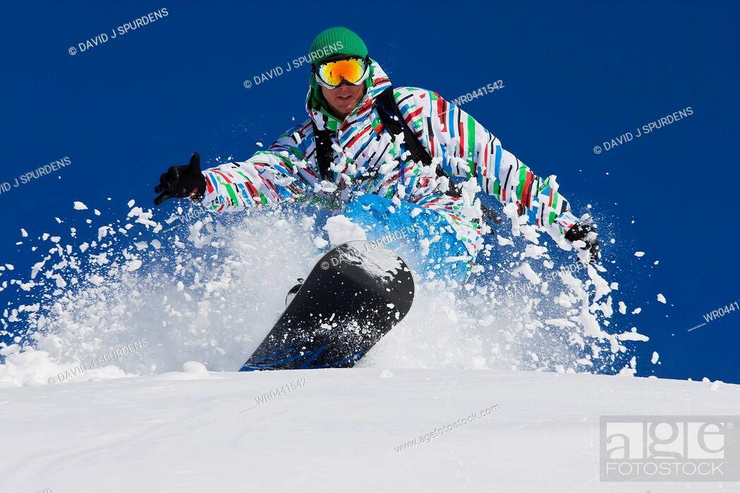 Stock Photo: A snowboarder riding hard through the fresh powder snow smiles.