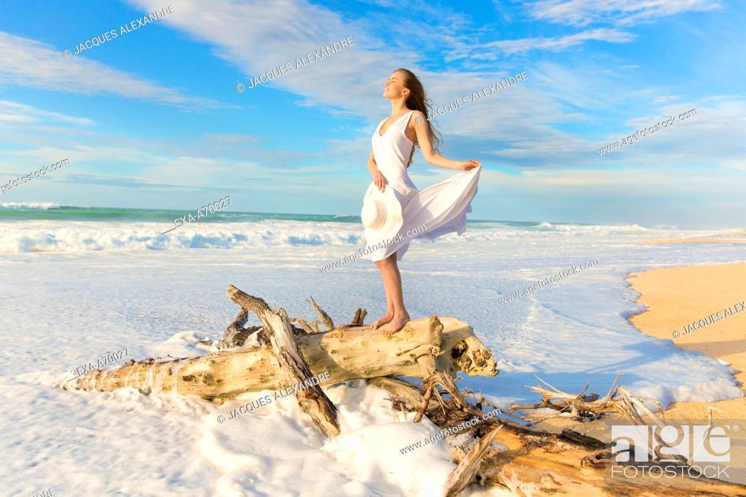 Imagen: woman standing on trunk at beach.