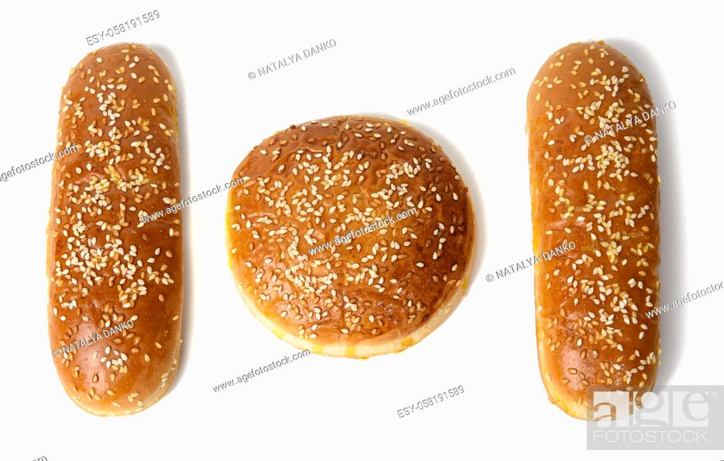 Stock Photo: round bun and baked oval hot dog bun, baked goods sprinkled with sesame seeds and isolated on white background, top view.
