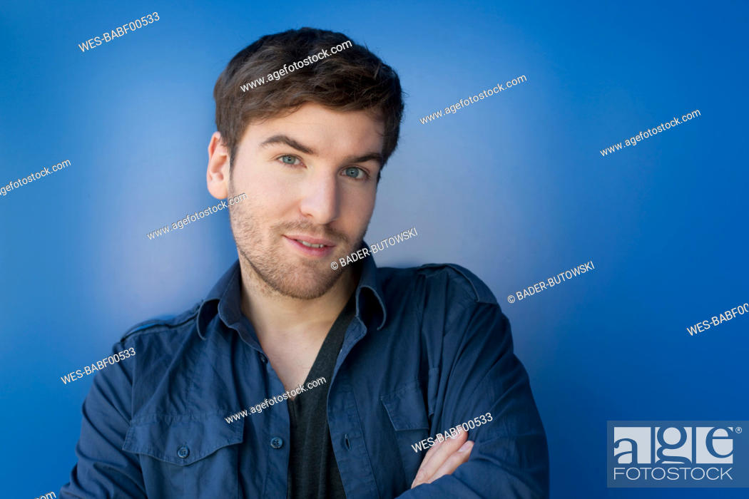 Stock Photo: Germany, Leipzig, Young man standing with arms crossed, smiling, portrait.