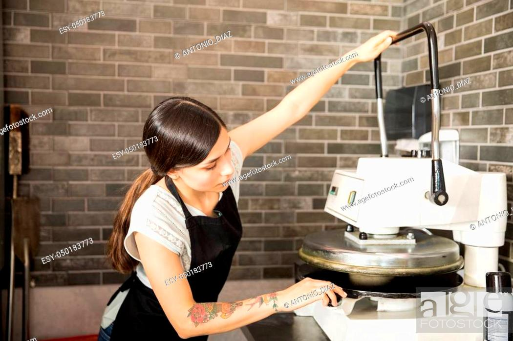 Stock Photo: Busy woman wearing black apron concentrating on using dough press machine to make pizza bread in kitchen at pizza shop.