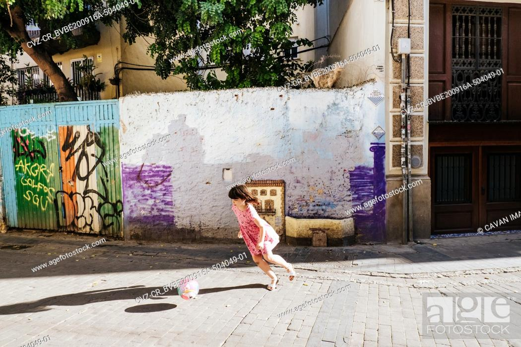 Imagen: young girl playing football/soccer in a colorful street.