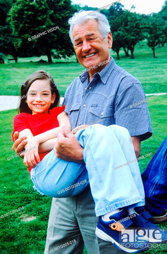 Stock Photo: Portrait of grandfather carrying his granddaughter in his arms.