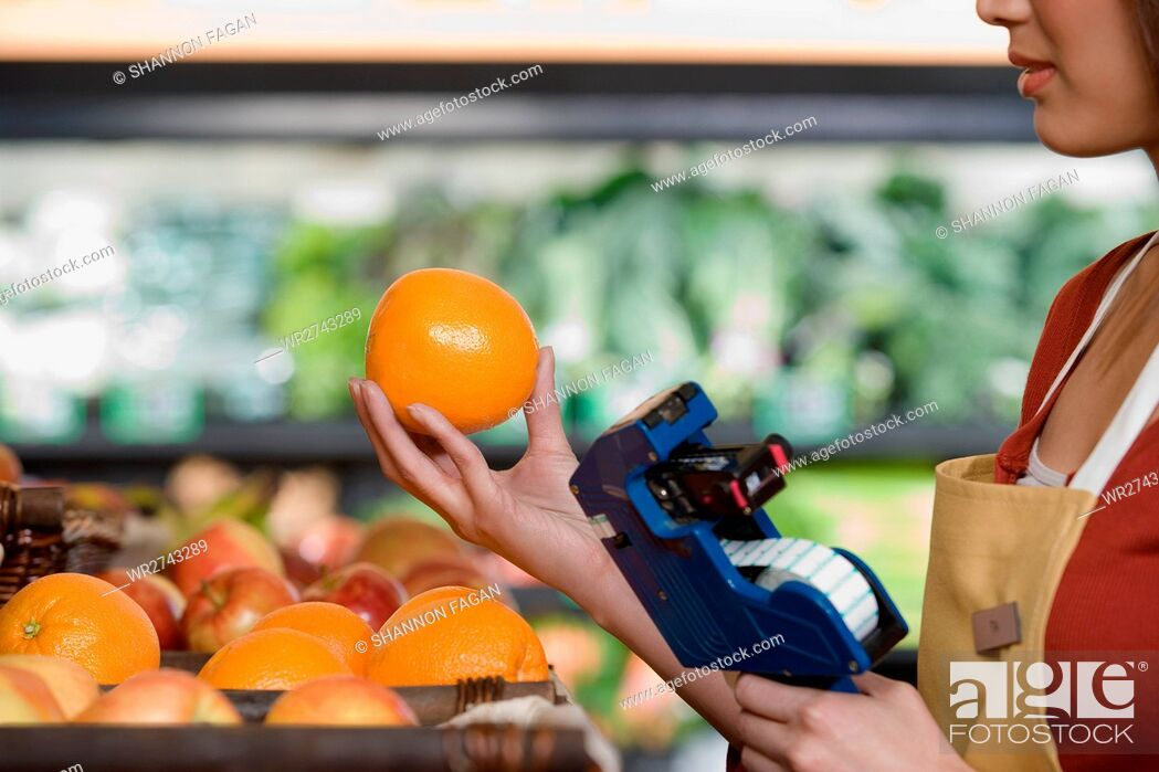 Stock Photo: sales assistant pricing an orange.