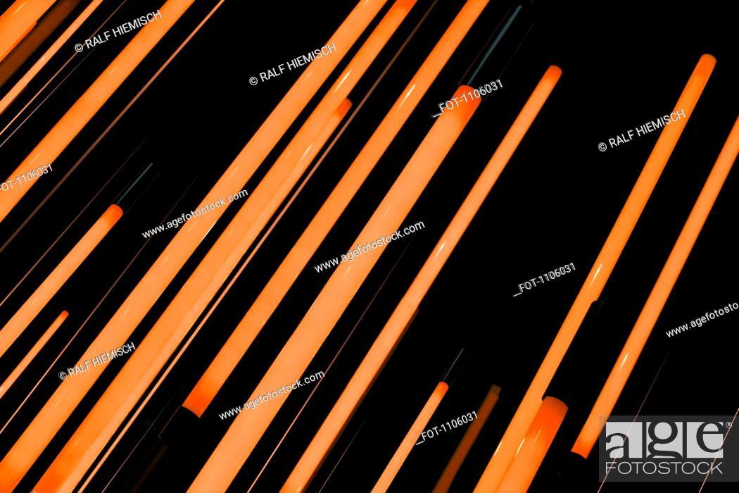 Stock Photo: Neon orange rods of glowing light.