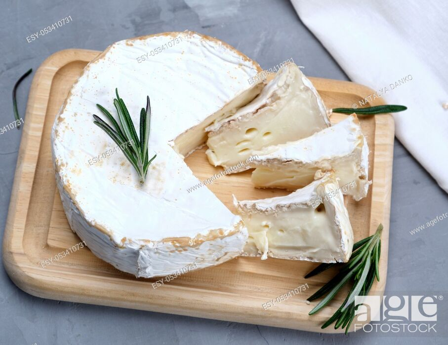 Stock Photo: round brie cheese on a wooden board, gray background , top view.