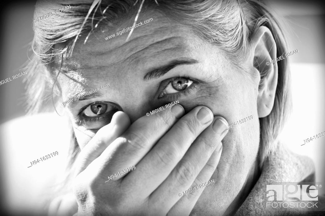 Stock Photo: Central European woman portrait with hand on her mouth and looking at the camera.